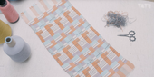 photograph of a pastel weaved piece of material with reels of threads and scissors