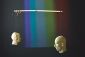 Two moulds of human heads hanging on a mobile with a rainbow behind them
