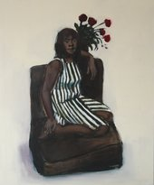 a woman wears a stripey dress and sits on a chair with a vase of roses in the background