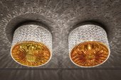 An image of two lead crystal lamps with a mixture of palm oil and cognac applied to the inside. They cast patterns of light onto a ceiling