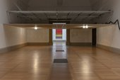 An empty gallery room with a false ceiling inserted two thirds up the walls and covering half of the gallery space
