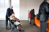 A wheelchair user arriving at the information desk, Tate Liverpool