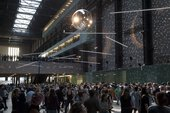 a large discoball is suspended from the ceiling of the turbine hall. people dance below.