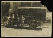Black and white photograph of four people standing next to a medical supplies van or ambulance