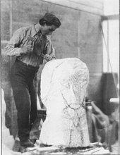 Black and white photograph of Henri Gaudier Brzeska carving hieratic head of Ezra Pound.