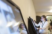 Female volunteer guide operates one of the digital screens in Tate Britain