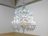 A large chandelier glass is a mixture of clear, blue and orange colours and the lights look like candles
