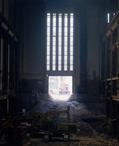 Interior view of Bankside Power Station after plant removal, showing rubble and digger in the foreground 1995