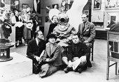 A black and white photograph of Diana Brinton-Lee, Salvador Dalí (in diving suit), Rupert Lee, Paul Éluard, Musch Éluard, ELT Mesens at the International Surrealist Exhibition in London (1936).
