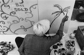 Black and white photograph of artist from above as he sits on the floor and draws a palm tree onto a board