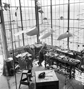 Black and white photograph of Alexander Calder standing in his studio with one of his mobiles hanging above it