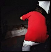 Chris Verene Untitled Red Back 1997 photograph of a man taking a picture of a woman posing on a bed