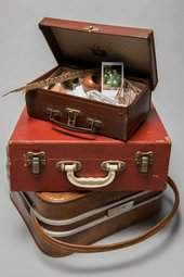 A pair of three brown suitcases are piled on top of each other. The top one is open with random objects inside including a feather and a photograph