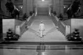 Shezad Dawood film still from A Mystery Play 2010 showing a man dressed in a white suit going up a wide marble staircase