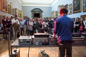 A DJ standing at a DJ booth in front of a crowd of people in one of the galleries at Tate Britain