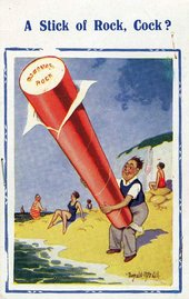 Donald McGill A Stick of Rock Cock a cartoon of a man standing on the beach holding an enormous stick of rock sweet at his crotch pointing upwards