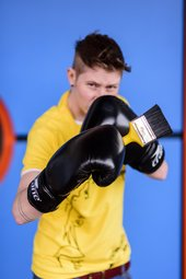 A member of Tate Collective Liverpool boxing with a paintbrush