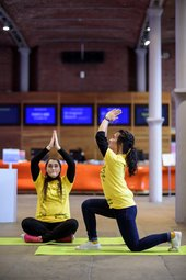 Two members of Tate Collective doing yoga in Tate Liverpool's foyer