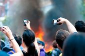 'A crowd of spectators using their mobile phones to capture footage of a burning police car on Queen St. W. in Toronto during the 2010 G20.'