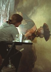 A conservator removing varnish from a painting