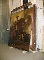 A painting leaning against the wall in the storage room