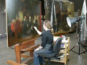 A person sitting in front of a painting and gently removing the varnish with a cotton bud