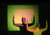 Figure with arms outstretched in front of a square projection of green and yellow lights