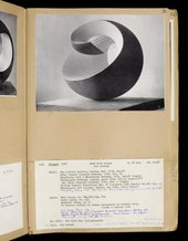 Photograph of a page in Hepworth's sculpture records showing a black and white photograph of sculpture Pelagos with typewriter record text underneath