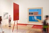 People at Tate Britain walking in front of David Hockney's A Bigger Splash
