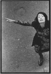 Black and white photo from above of Asian woman with her arms spread, facing up at the photographer