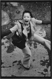 Black and white photograph of Asian woman dancing in the street with mouth wide open looking up at photographer in the window above.