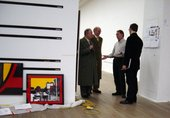 Gilbert and George next to hanging rails for a photo piece