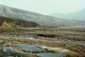 Roni Horn Man at hot spring, Strútur, Iceland 1990 Photograph of mountainous landscape with hot springs and a man paddling in pools