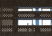 Detail of the perforated brickwork design and the horizontal windows on the new building