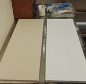 Two stretched cotton canvases – one unprimed (left) and the other primed with white alkyd paint (right) – being used as mock-ups for cleaning tests.