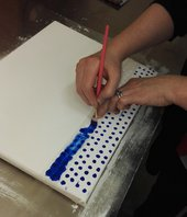 Paintings conservator Rachel Barker applying blue oil paint through a stencil to recreate the Ben Day dots on Whaam! for a mock-u-