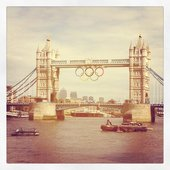 A photograph of Tower Bridge with the Olympic rings suspended from the bridge