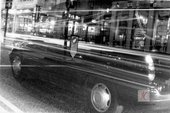 A photograph of a black cab on Oxford Street in black and white