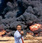 kennardphillipps Photo Op 2007 Tony Blair taking a picture of himself on a mobile phone against the backdrop of smoke and flames