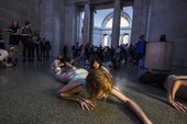 A performance artist crawling on the floor of Tate Britain