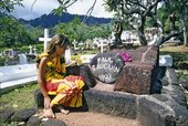 A local girl sitting next to Paul Gauguins grave in Atuona Hiva Oa on the Marquesas Islands French Polynesia