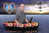 Martin Parr sits in a boat covered in flowers with planes flying up ahead