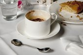 photograph of coffee, double ended spoon and cake on a white tablecloth