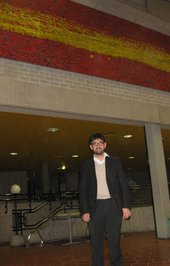 Mark Godfrey, co-curator of Gerhard Richter: Panorama at Tate Modern standing underneath Richter's 20-metre long painting Stroke (on Red) 1980