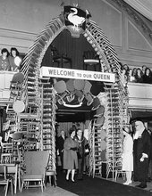 Queen Elizabeth II entering High Wycombe Town Hall through an archway made of locally made chairs, April 1962
