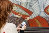 An image of the Tate Britain mobile tour on a phone in front of an artwork in the gallery