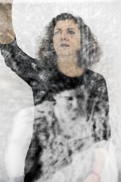 Photograph of the artist with her arm raised with a projected image of a female portrait on her