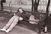 Two men sleeping on a bench