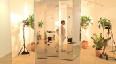 Image shows a room full of mirrors and plants and a woman standing in white leggings side on