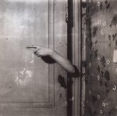 Paul Nouge Le bras revelateur from Subversion des images 1929 to 1930 Black and white photograph of an interior where an arm emerges from behind a door with a finger pointing to the left